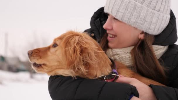 majitel hladí jeho milovaný pes a úsměvy. dívka s lovecký pes chodí v zimě venku
