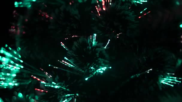 Christmas tree in room shines with blue, red lights. artificial Christmas tree is decorated with a garland and glows with beautiful colored lights.