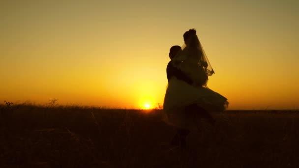 Mladá nevěsta a ženich krouží na pozadí romantické rudý západ slunce. Líbánky. Vztah mezi mužem a ženou