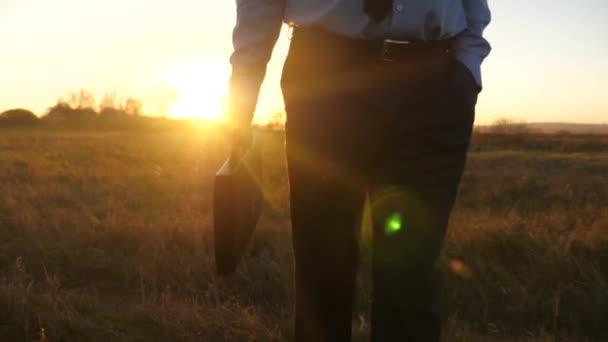 Obchodní muž s aktovkou v ruce a v obleku jde při západu slunce v záři slunce. Detail