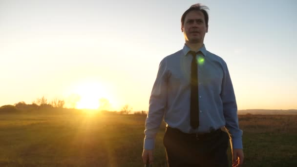 Business man with briefcase in his hand and in blue shirt with tie walks at sunset into glare of sun