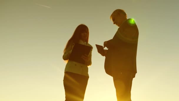 Business man with tablet and business woman with tablet in business suits discuss plan and schedule of work at sunset and laughs. Business meeting with working partner. Conversation
