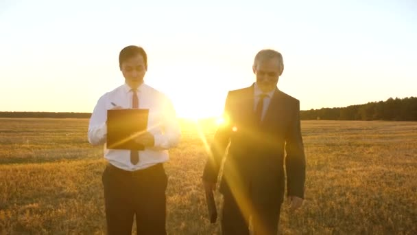 Businessmen with tablet and briefcase in their business suits discuss plan for working together at sunset in glare of sun and smile. Business meeting with working partner. Dialogue
