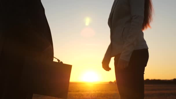 Business man and business woman made deal in glare of setting sun, shook hands with and handed over briefcase with documents. Close-up