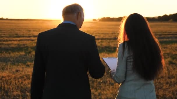 An elderly businessman in serious suit with briefcase in his hand gives working plan to young business woman of company in evening in bright sun on positive