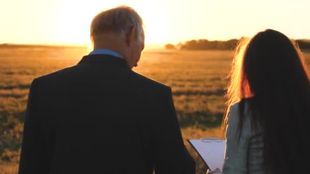 An elderly businessman in serious suit with gives working plan to young business woman of company in evening in bright sun. Slow motion