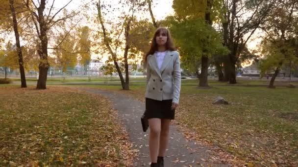 Geschäftsfrau mit schwarzer Aktentasche geht Weg im Herbstpark