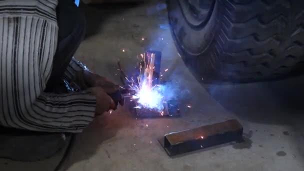 svářeč připojí k složitých struktur pomocí elektrické svařování kovových dílů. barevné jiskry létají na stranu