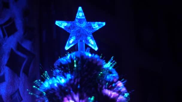 Umělý vánoční stromek zdobí věnec a vánoční hvězda. krásná záře vánočního stromu v temné místnosti