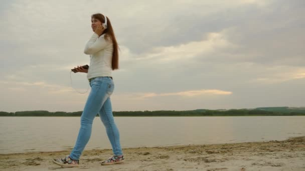 beautiful girl in headphones goes on beach in evening with a tablet and listens to music.