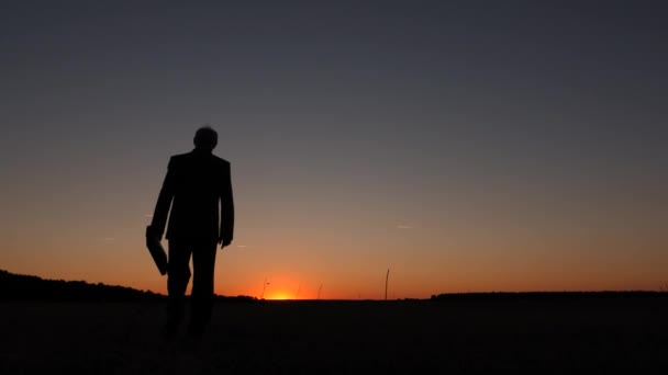 silhouette of businessman with briefcase walking at sunrise on a background of blue sky