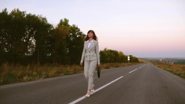 business woman with black briefcase walks in light suit and white high-heeled shoes goes outside city along asphalt with white markings