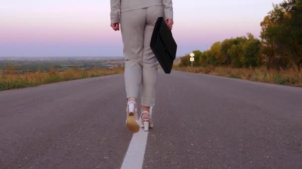 podnikatel žena nosí černý kufřík s dokumenty v levé ruce, žena chodí na asfaltu v kalhotách a bílé boty s vysokými podpatky