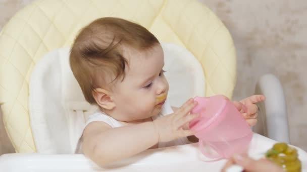 Kleinkind sitzt im Kindersitz und trinkt Wasser aus Kinderglas