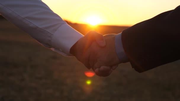 handshake při západu slunce. v modré košili a sako a muž v bílé košili potřást rukou při západu slunce v paprscích krásný západ slunce. detail.