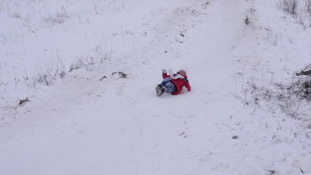 Happy girl rolls from snowy mountain on sleigh in white snow in winter and smiles. Christmas Holidays. Slow motion