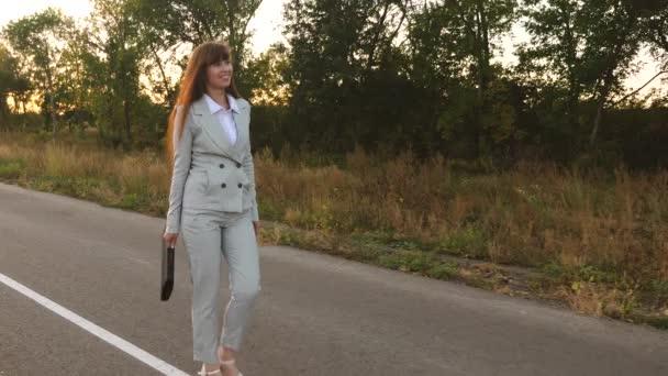 obchodní žena s černou aktovkou chodí ve světle oblek a bílá na vysokém podpatku boty procházky po asfaltu s odznaky, pohled z předu