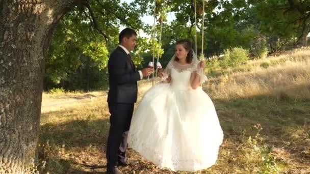 Glücklich Bräutigam Anzug und die Braut im weißen Kleid trinken Champagner aus schönen Weingläser und fahren auf Schaukel im Park lächelnd zu einander. Paar in Liebe trinken Wein