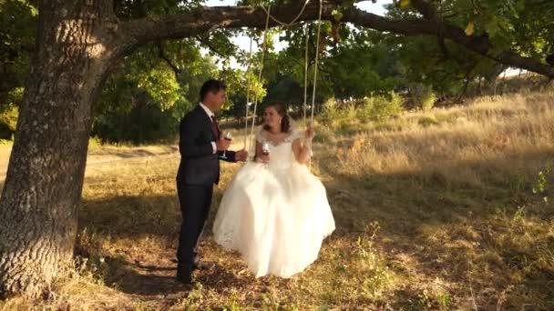 glücklich Bräutigam im Anzug rollt auf Schaukel Braut im weißen Kleid trinken Champagner aus schönen Weingläsern im Park lächelnd zueinander. Verliebtes Paar trinkt Wein