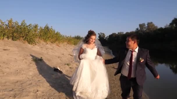beautiful bride in white dress and groom in a suit running barefoot on beach along the river. happy loving couple.