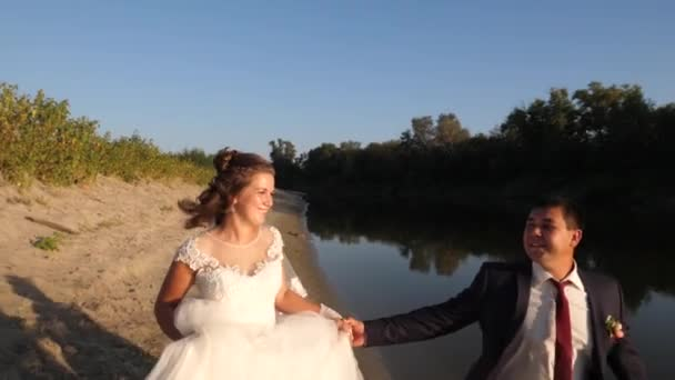 beautiful bride in white dress and groom in a suit running barefoot on beach along the river. close-up
