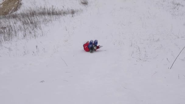 Girl rolls from high snowy mountain on snow saucer and laughs. Christmas. Games with snow on frosty day