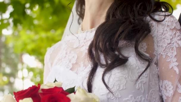 Mädchen im weißen Kleid hält einen Strauß roter und weißer Rosen in der Hand. Nahaufnahme.