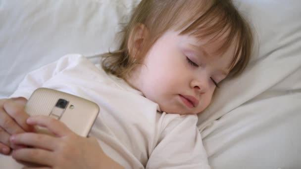 Roztomilé dítě spí v posteli s smartphone. dítě leží na polštáři a drží tablet