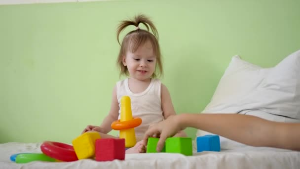 child and mom play with colorful cubes on bed. Educational toys for preschool and kindergarten children. Toy for Kid. child plays in room on the bed with cubes and builds the tower with mother