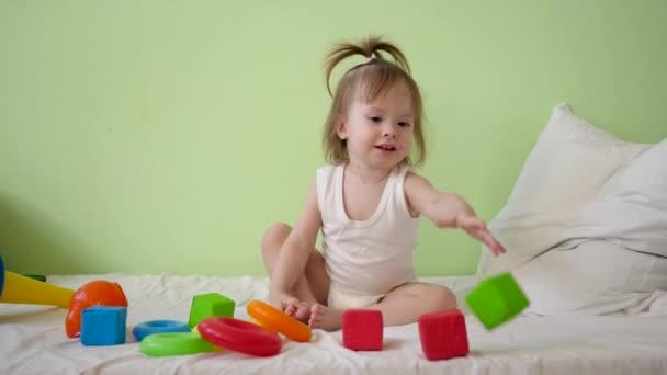 dítě si hraje s různobarevné kostky na bílé posteli a hází je své matce. Vzdělávací hračky pro školky a školky děti. Hračka pro děti.