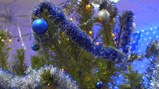 zelené, velké, krásné vánoční strom v místnosti zařízené girland, barevné koule a pozlátko