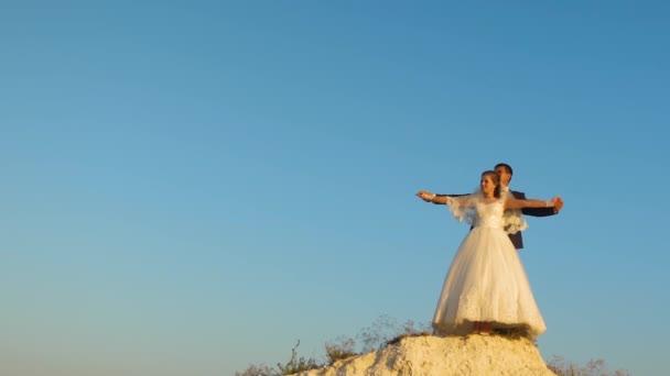 Gli amanti della sposa e dello sposo che tengono le mani contro il cielo blu e sorridente. Luna di miele. Il concetto di vita familiare. relazioni sentimentali tra uomini e donne
