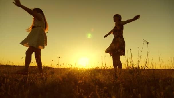 boldog lány táncol a sugarak a gyönyörű naplemente a parkban. Tizenéves lányok, hosszú hajú örvény repülés alatt sugarai arany naplemente. Lassú mozgás.