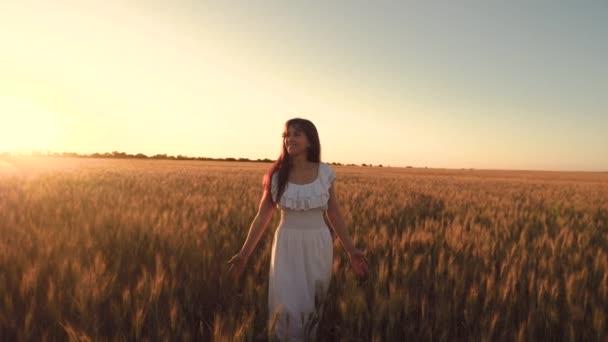 glückliches Mädchen geht auf einem Feld aus gelbem Weizen in den Strahlen des schönen Sonnenuntergangs. Mädchen berührt die Ähren des reifen Weizens. Zeitlupe
