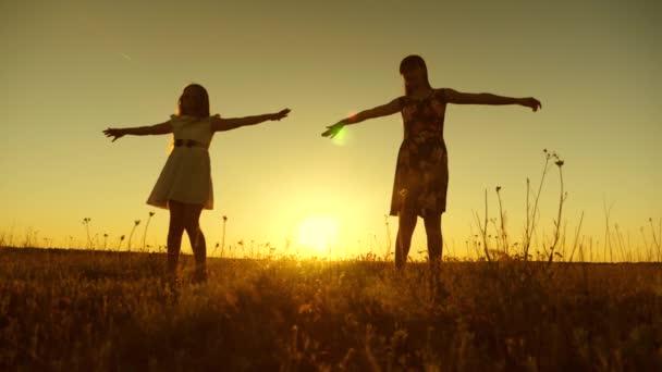 Dospívající dívky jsou víření při západu slunce zlaté slunce. Zpomalený pohyb.