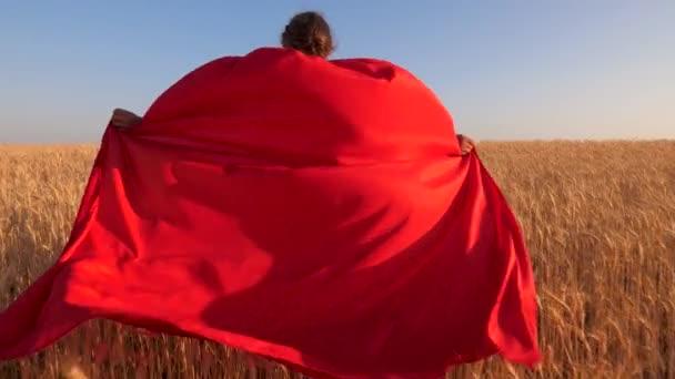 gyermek fut át mező a búza, a gyönyörű piros zöld kék ég ellen. közelről. tini lány szuperhős játszik egy piros köpenyt. közeli kép: