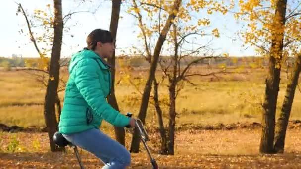 gyönyörű lány Kerékpár túrák az út a háttér sárga fák őszi parkban oldalán. Sport, biciklizés.
