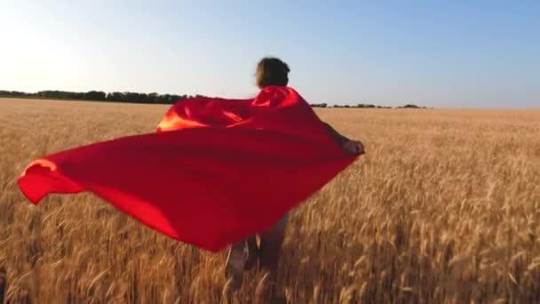 Ragazza super eroe che gioca nel campo di frumento. Slow motion