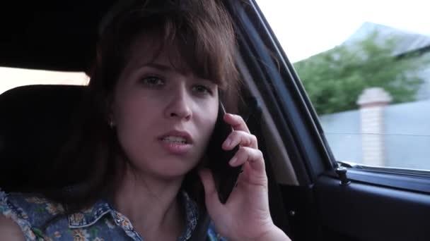 Mladá dívka se mluví o telefonu a jízdě autem na silnici město s otevřeným oknem