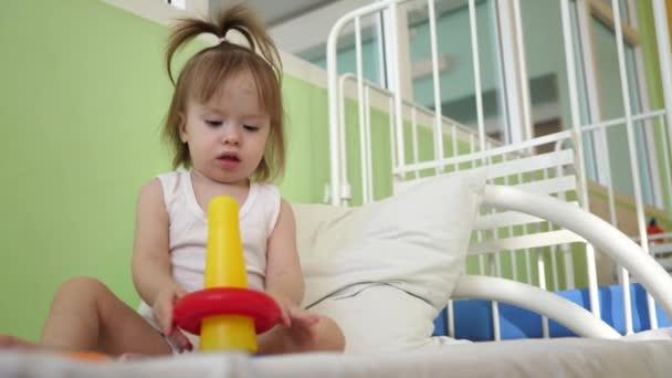 Dítě a dítě děti hrají na posteli s pyramida a barevné kroužky. Vzdělávací hračky pro školky a školky děti. Hračky pro dívky.