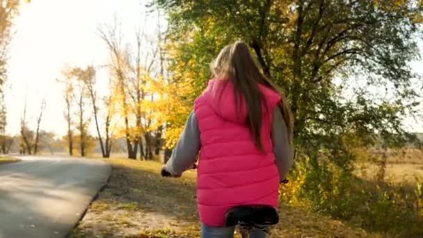 fiatal lány lovaglás kerékpár az úton az őszi park, és mosolygott. Lassú mozgás.