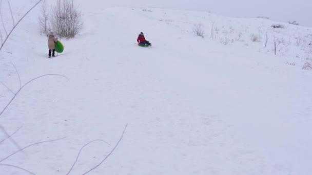 glückliches Mädchen gleitet von einer hohen Schneerutsche eine aufblasbare Schneeröhre. Kinder spielen im Winter im Park in den Weihnachtsferien. Kinder rodeln von einem hohen Hügel