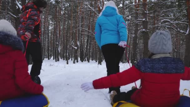 happy dad and mom pull sleds with children in winter forest. parents play with children in a snowy park in winter. happy family sledding during christmas holidays
