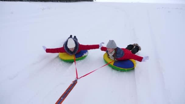 boldog gyermekek, szánkózás télen egy felfújható hó cső, és integetett a kezével. a gyermekek nevetni és örvendezni. lány játszik a winter Park, a karácsonyi ünnepek