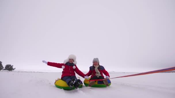 Glückliche Mädchen rodeln im Winter im Schnee und winken mit den Händen. Kinder rutschen auf einer aufblasbaren Schneeröhre und lachen und jubeln. Kinder spielen in den Weihnachtsferien im Winterpark. Zeitlupe