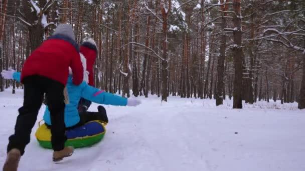 Šťastné děti jezdit jejich máma na saně a nafukovacích gumových kruhů v borovém lese. šťastná rodina Maminka a děti hrají v zimě parku a lesa pro vánoční svátky. Zpomalený pohyb