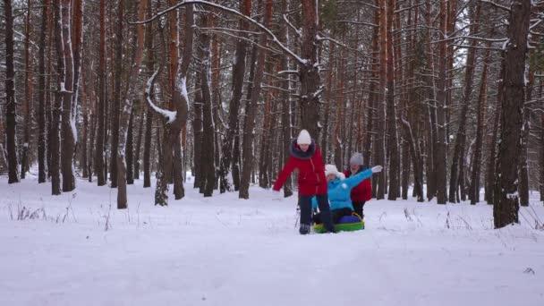 Lustige Kinder fahren ihre Mutter auf Schlitten und eine aufblasbare Snow-Tube im Pinienwald. glückliche Familie Mutter und Kinder spielen im Winter Park und Wald für die Weihnachtsferien.