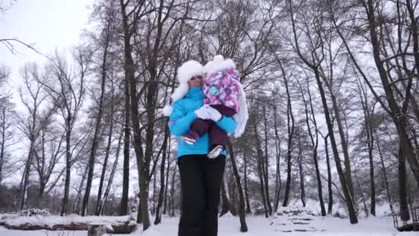 Glückliche Mutter trägt kleine Tochter im Arm bei einem Spaziergang durch den verschneiten Park im Winter. Elternteil geht mit Kind im Park und lächelt. Weihnachten