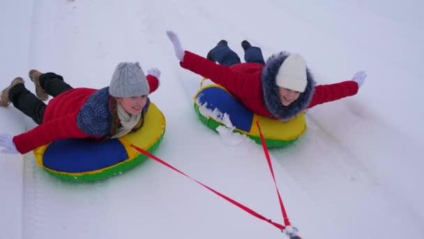 Lányok a piros zakó kört hóban, télen egy felfújható hó cső és a játék a super heroes. boldog lány pihentető téli Park karácsonyi ünnepek. Lassú mozgás
