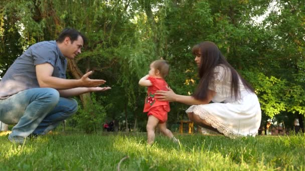 Happy baby playing with parents in park. Merry mom and dad are walking with their daughter in park. Family values